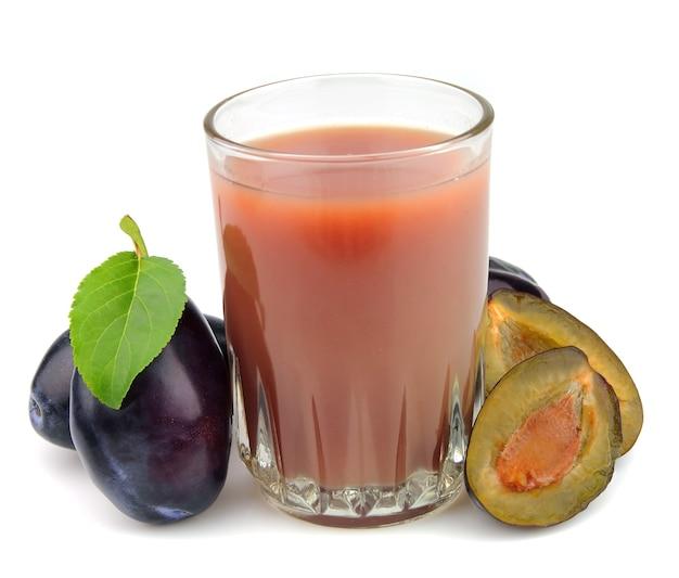 Świeże śliwki i pełną szklankę soku ze śliwek na białym tle