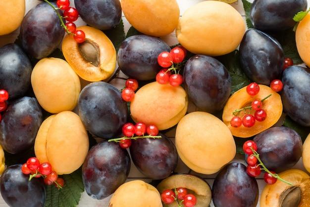 Świeże śliwki, morele i czerwone porzeczki jagody z liśćmi na lekkim stole.