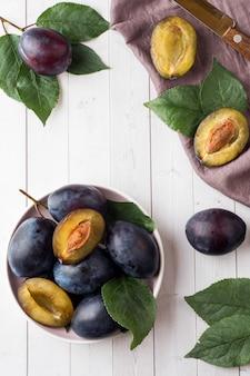 Świeże śliwkowe jagody na talerzu z liśćmi na lekkim stole. pionowy