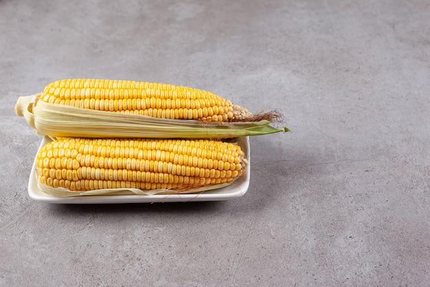 Świeże słodkie kłosy kukurydzy na białym talerzu