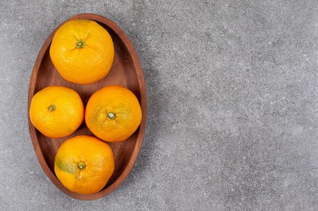 Świeże słodkie mandarynki na drewnianej desce kuchennej