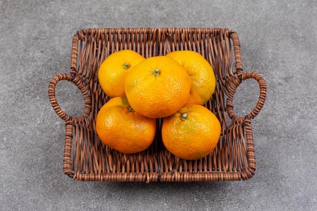 Świeże słodkie mandarynki na wiklinowym koszu