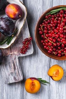 Świeże słodkie owoce śliwki całe i pokrojone w talerz z liśćmi rozmarynu na starej desce do krojenia z jagodami czerwonej porzeczki w drewnianej misce, szara powierzchnia drewna, widok z góry
