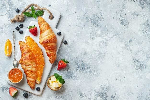Świeże słodkie rogaliki z masłem i dżemem pomarańczowym na śniadanie. śniadanie kontynentalne na białym betonowym stole. widok z góry. leżał płasko.