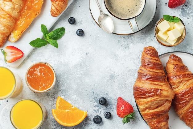 Świeże słodkie rogaliki z masłem i dżemem pomarańczowym na śniadanie. śniadanie kontynentalne na białym betonowym stole. widok z góry z miejsca na kopię. leżał płasko.