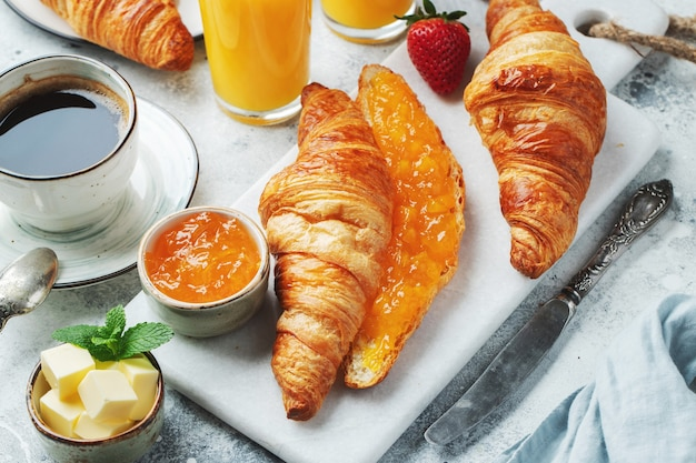 Świeże słodkie rogaliki z masłem i dżemem pomarańczowym na śniadanie. śniadanie kontynentalne na białym betonowym stole.