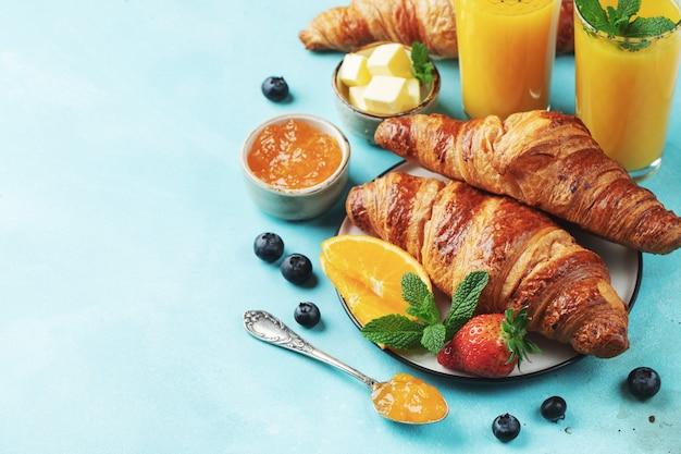 Świeże słodkie rogaliki z masłem i dżemem pomarańczowym na śniadanie. śniadanie kontynentalne na jasnym betonowym stole. widok z góry z miejsca na kopię. leżał płasko.