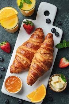 Świeże słodkie rogaliki z masłem i dżemem pomarańczowym na śniadanie. śniadanie kontynentalne. widok z góry. leżał płasko.
