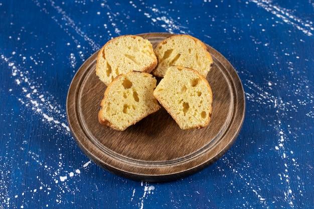 Świeże, smaczne ciasta w plasterkach umieszczone na drewnianym talerzu.