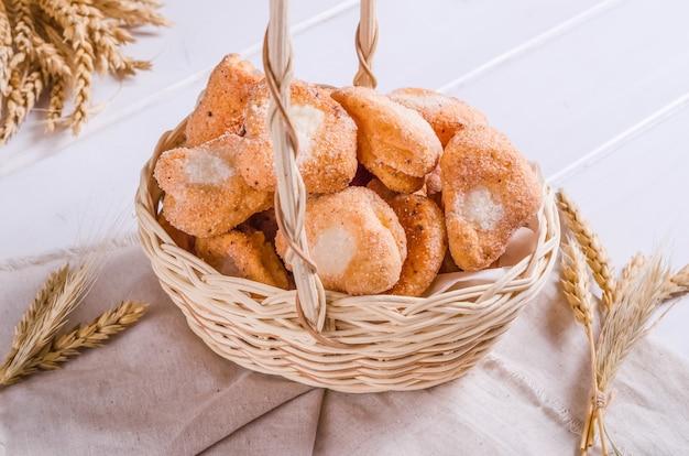 Świeże smaczne ciasteczka z cynamonem i cukrem w wiklinowym koszu na białym drewnianym tle