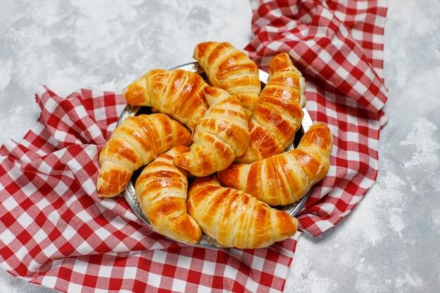 Świeże, smaczne domowe rogaliki na szaro-białym. ciasto francuskie