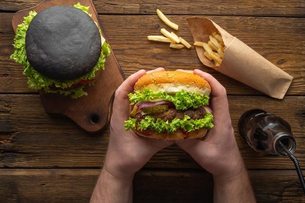 Świeże, smaczne hamburgery z frytkami, pić na drewnianym stole widok z góry.