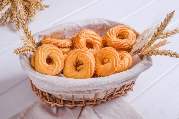Świeże smaczne kruche ciasteczka w wiklinowym koszu na białym drewnianym tle