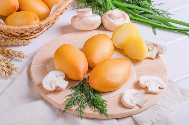 Świeże smaczne placki faszerowane ziemniakami i grzybami na okrągłej drewnianej desce na białym drewnianym tle