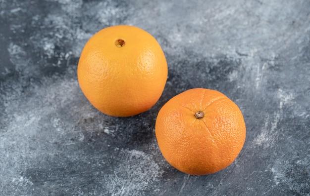 Świeże, smaczne pomarańcze na marmurowym stole.