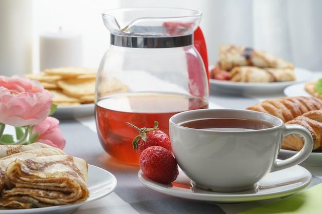Świeże, smaczne śniadanie z herbatą i bułeczki na jasnym tle.