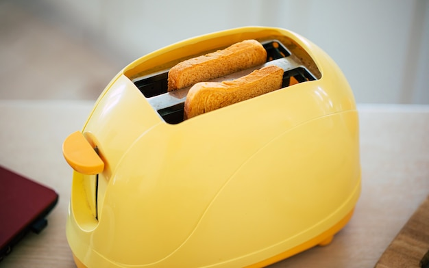 Świeże smaczne tosty z żółtego tostera na pięknym kuchennym stole w domu