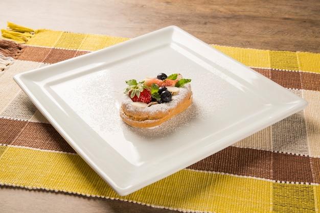 Świeże smażone churros z dyni z czerwonymi owocami na talerzu.