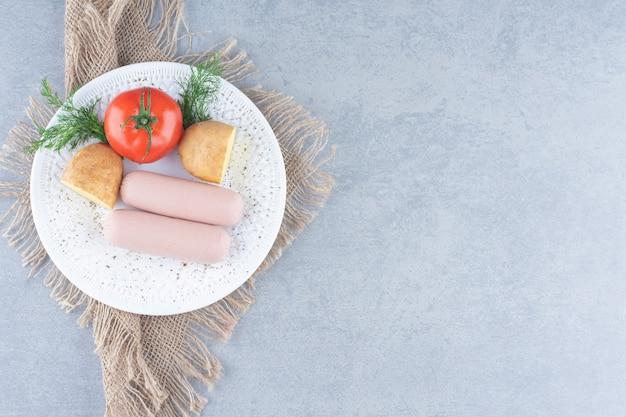 Świeże śniadanie. kiełbasa gotowana z pomidorem i ziemniakami.