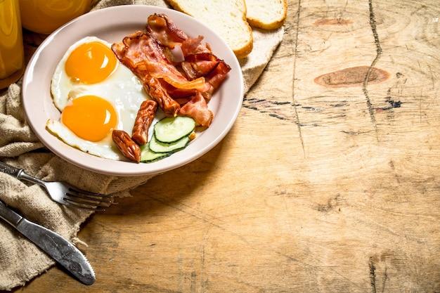 Świeże śniadanie. sok pomarańczowy z jajkiem sadzonym, boczkiem i kromkami chleba. na drewnianym stole.