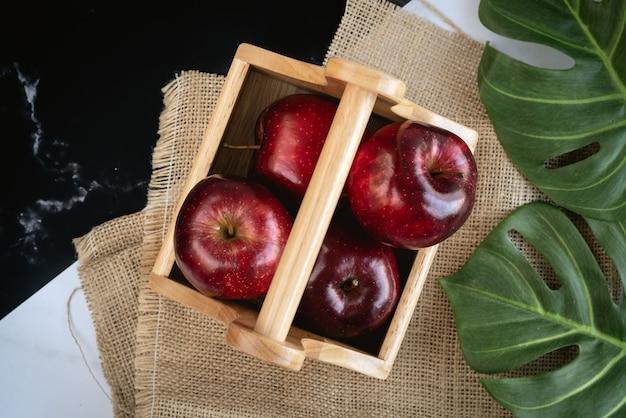 Świeże, soczyste czerwone jabłka w drewnianym koszu z zielonym liściem monstera na worze i czarno-białą marmurową powierzchnią na nadchodzący festiwal dziękczynienia