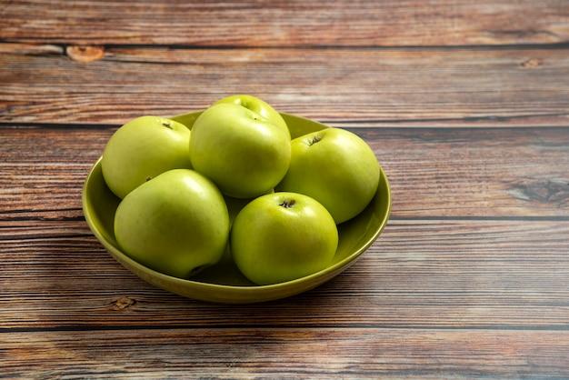 Świeże, soczyste, dojrzałe zielone jabłka w misce na drewnianym stole