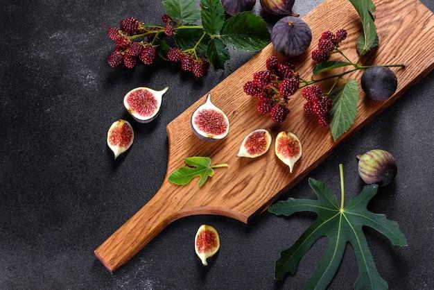 Świeże, soczyste figi i jeżyny na ciemnym tle. zbieranie jagód i owoców