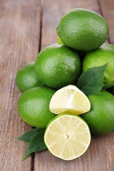 Świeże soczyste limonki na starym drewnianym stole