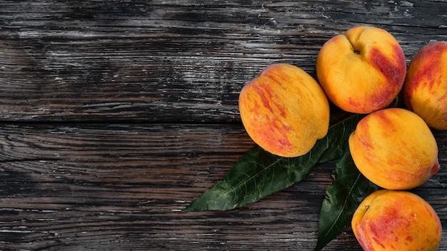 Świeże soczyste owoce brzoskwinie z liśćmi na ciemnym drewnianym tle rustykalnym, widok z góry z miejscem na kopię