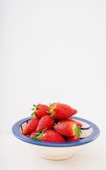 Świeże, soczyste truskawki w ceramicznej misce na białym tle nad białym biurkiem. widok z boku. skopiuj miejsce