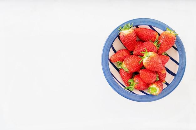 Świeże, soczyste truskawki w ceramicznej misce na białym tle nad białym biurkiem. widok z góry. skopiuj miejsce