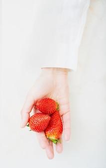 Świeże, soczyste truskawki w kobiecej dłoni na białym biurku. widok z góry. skopiuj miejsce