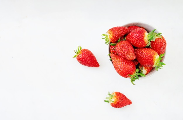 Świeże, soczyste truskawki w misce izolowanych na białym biurku. widok z góry. skopiuj miejsce