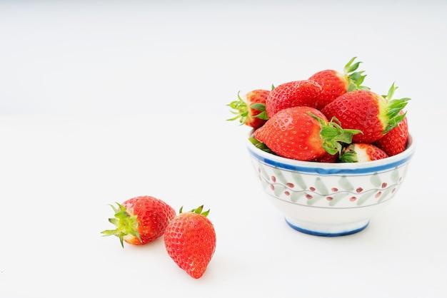 Świeże, soczyste truskawki w misce na białym tle na białym biurku. widok z boku. skopiuj miejsce