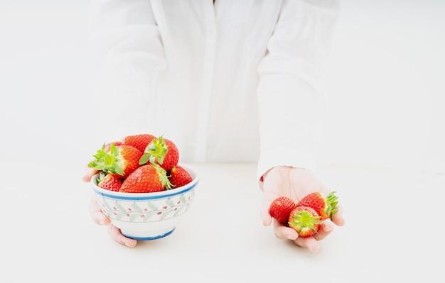 Świeże, soczyste truskawki w misce w rękach kobiet na białym biurku. widok z boku. skopiuj miejsce