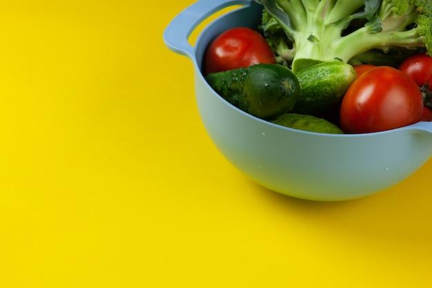 Świeże, soczyste warzywa w żółtym stole. surowe jedzenie i wegetarianizm