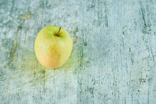 Świeże soczyste zielone jabłko na białym tle na marmurowym tle.
