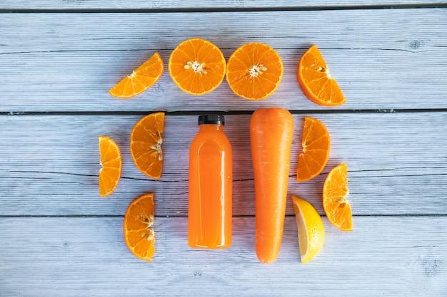 Świeże soki detox z owoców i warzyw w butelkach na podłoże drewniane