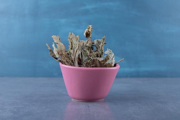 Świeże, suche liście w różowym kolorze na szarym tle. zdjęcie poziome.