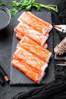 Świeże surimi z mięsa kraba z niebieskim zestawem krabów pływających, na kamiennej desce, na czarno