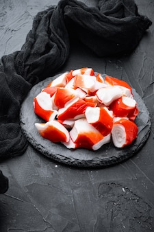 Świeże surimi z mięsa kraba z niebieskim zestawem krabów pływających, na kamiennej desce, na czarnym stole