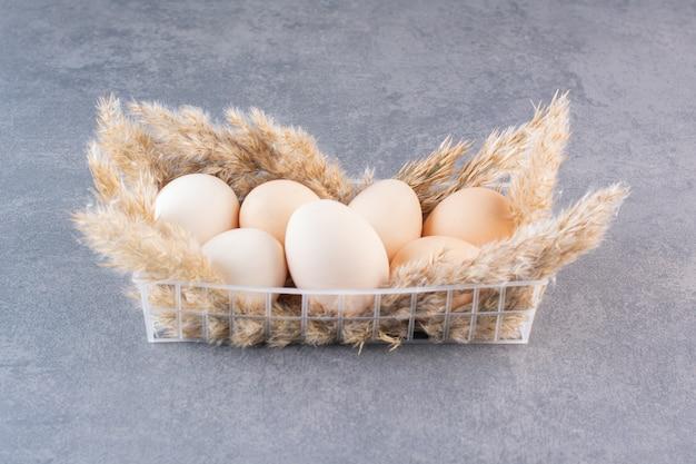 Świeże surowe białe jaja kurze z pszenicznymi kłosami umieszczone na kamiennym stole.