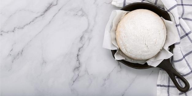 Świeże surowe ciasto drożdżowe domowej roboty odpoczynku na patelni żeliwnej na marmurowym stole płasko leżał.