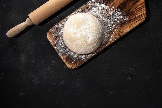 Świeże surowe ciasto na chleb lub pizzę na rustykalnej drewnianej posypce mąką.