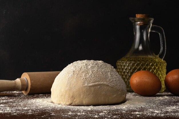Świeże surowe ciasto na chleb lub pizzę z jajkami i olejem na ciemnym drewnianym stole.