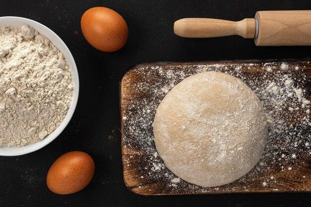 Świeże surowe ciasto na chleb lub pizzę z jajkami na ciemno z posypką mąką.