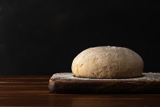 Świeże surowe ciasto na chleb lub pizzę z jajkami na ciemnym drewnianym stole.