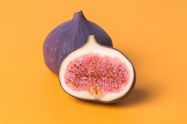 Świeże surowe figi i pół na pomarańczowym tle