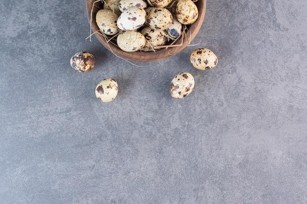 Świeże surowe jaja przepiórcze umieszczone na kamiennym stole.