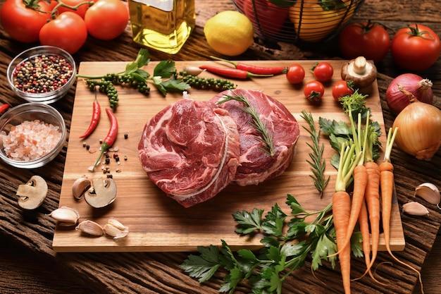 Świeże surowe kawałki wołowiny na desce do krojenia i więcej składników wokół